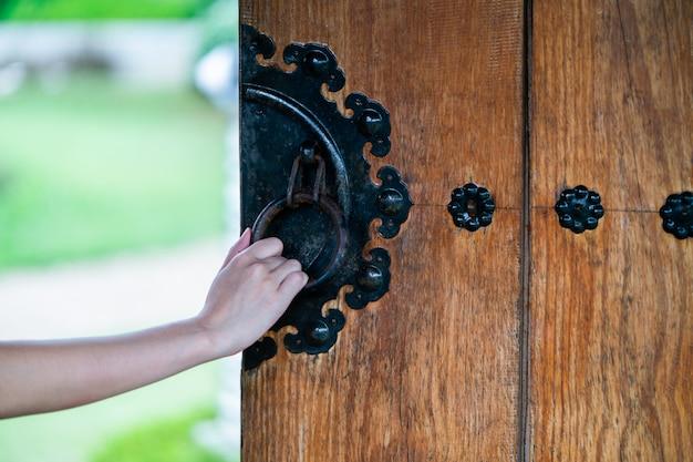Close up hand open chinese wooden door