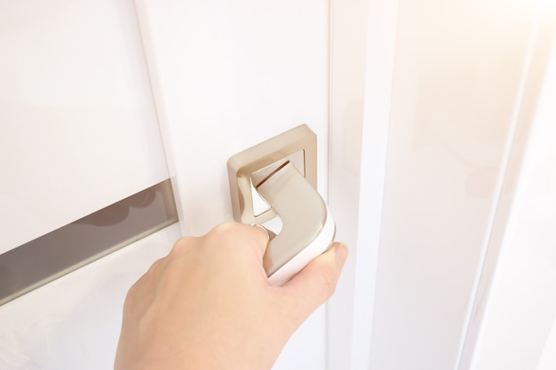 Close-up of hand opening door. hand holding chrome doorknob.