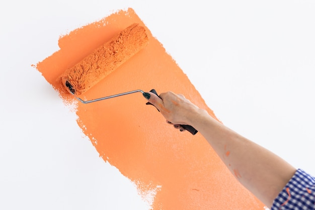 Close-up hand painting interior wall of home with paint roller. redecoration, renovation, apartment