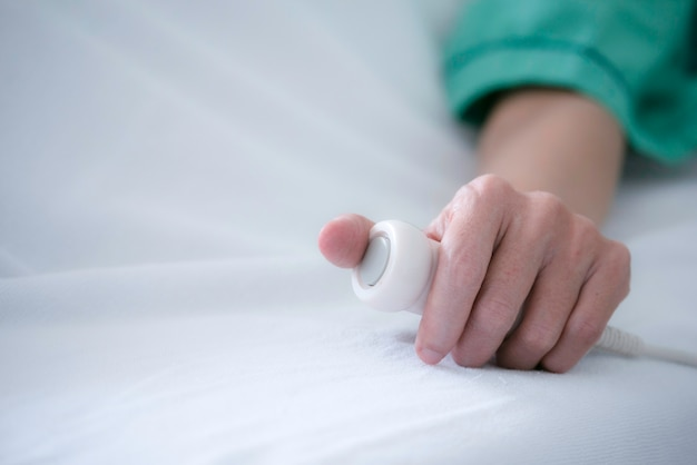 Close up hand of patient press the help button for nurse calling emergency in the hospital