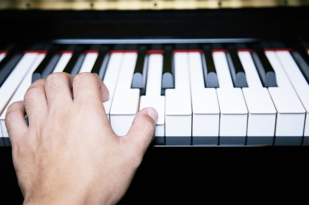 Close up of hand people man musician playing piano keyboard with selective focus keys.