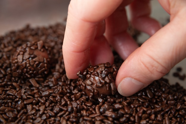 Close-up of hand picking up a delicious and traditional brazilian candy called brigadeiro in brazilian portuguese