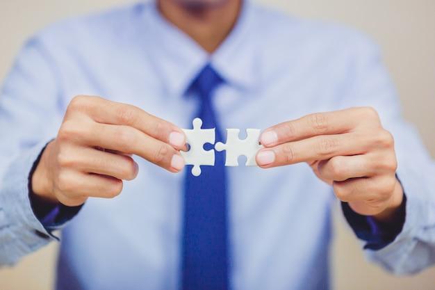 クローズアップ手は白いジグソーパズルのピースを1枚あたり白で作られた青い背景に置き、あなたのコンテンツのためにそれを配置する