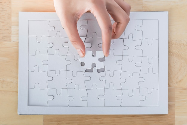 Close up of hand placing the last jigsaw puzzle piece, hand holding missing jigsaw puzzle piece down in to the place