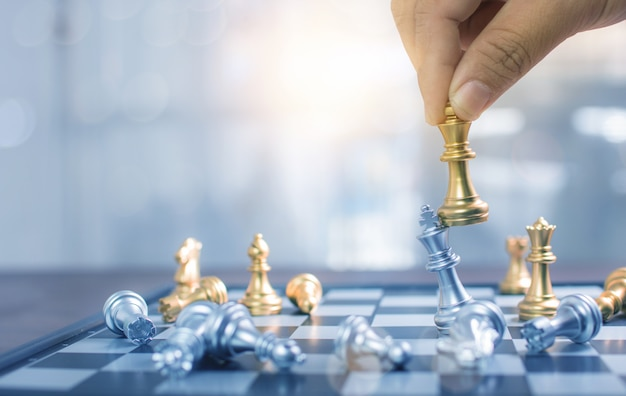 Close up hand playing chess and win in board game, strategy and planning business concept