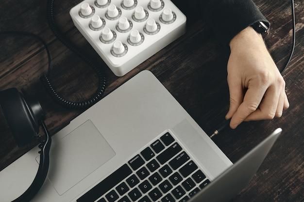 Крупным планом рука вставляет шнур наушников в музыкальный порт стереоразъема в ноутбуке retina
