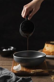 クローズアップ手にチョコレートをパンに注ぐ