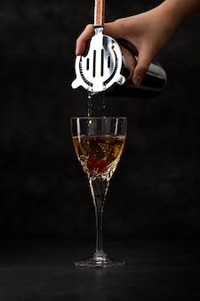 ガラスに飲み物を注ぐクローズアップ手