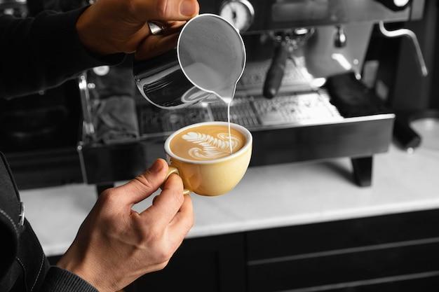 맛있는 커피 컵에 우유를 붓는 클로즈업 손