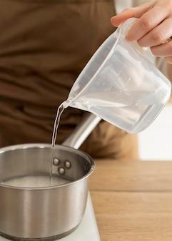 鍋に水を注ぐ手をクローズアップ