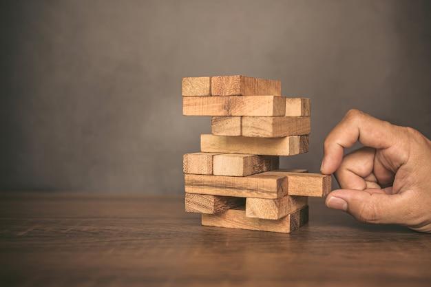클로즈업 손으로 타워 모양에 쌓인 다른 나무 블록에서 나무 블록을 당깁니다.