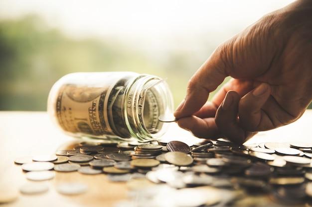 ガラスのボトルにコインを入れて手を閉じます。ビジネス、金融、貯蓄や管理のmone