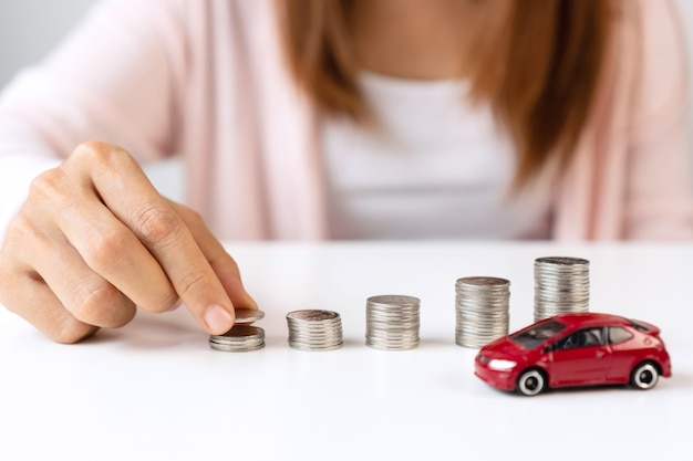 Close up of hand putting coin on pile coins for saving money. collect money to buy a new car, saving and car loan concept. flat lay