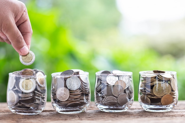 Close up hand putting coins into clear money jar