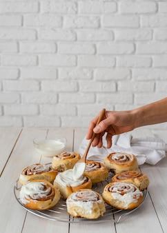 Крупным планом руки положить крем на булочки с корицей