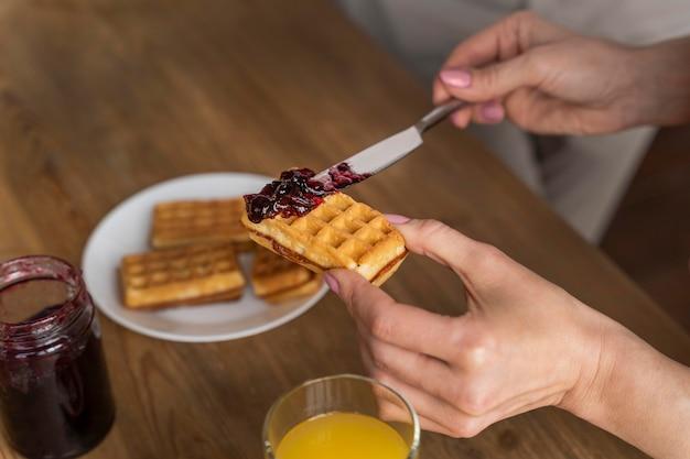 Chiuda sulla mano che mette la gelatina sulla cialda