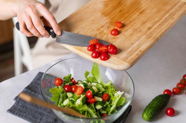 Chiuda sulla mano che mette i pomodori in insalata
