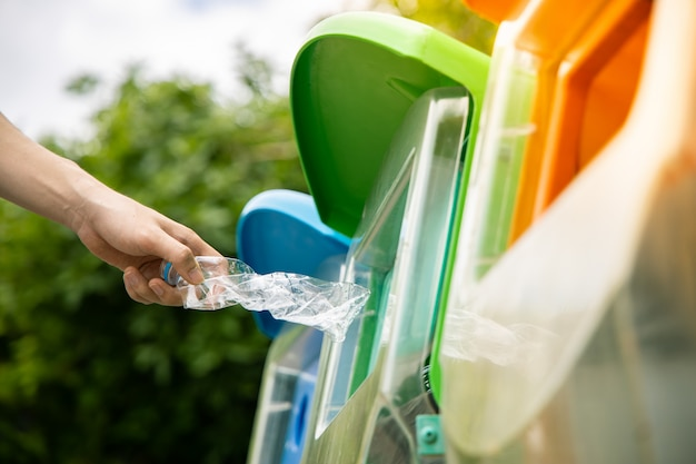 Close up , hand putting twisted empty plastic drinking water bottle into recycle bin in public.