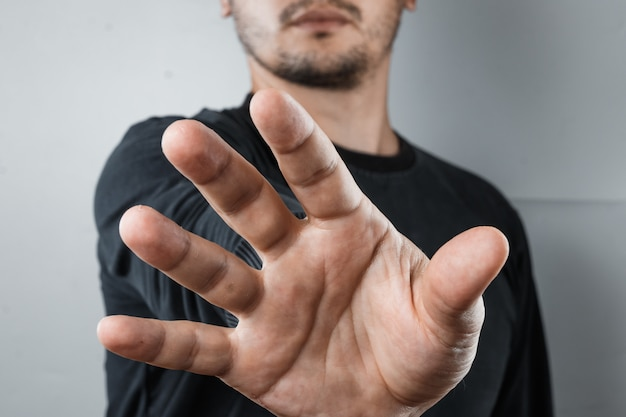 Close-up of hand raised to camera, gesture of stop