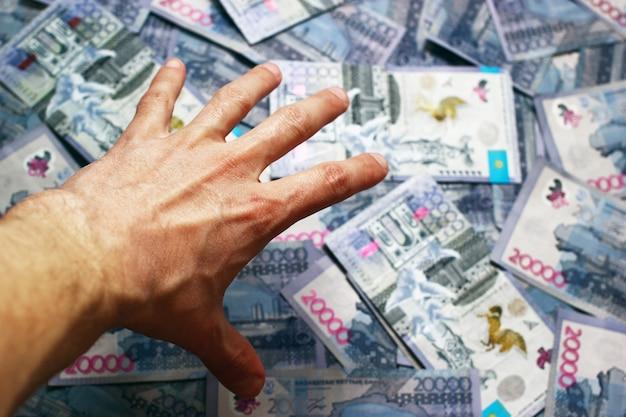 Крупным планом рука тянется к банкнотам казахстана 20 000 тенге, луч света