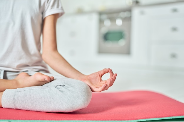Close up of hand of relaxed hispanic teenage girl in sportswear practicing yoga, meditating on a mat in the kitchen. home interior background. healthy lifestyle, relaxation concept