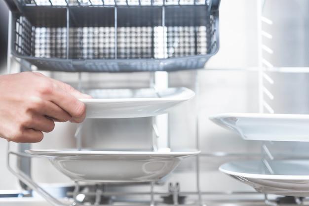 彼女のアパートのキッチンの食器洗い機で皿を取り除くクローズアップ手