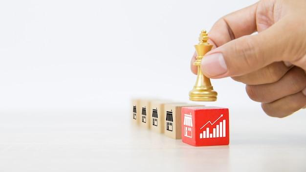 グラフとフランチャイズビジネスストアのアイコンが付いている木製のブロックスタック上のクローズアップの手選択キングチェスの駒。