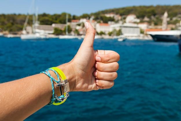 Chiuda sulla mano che mostra il pollice sul gesto al mare