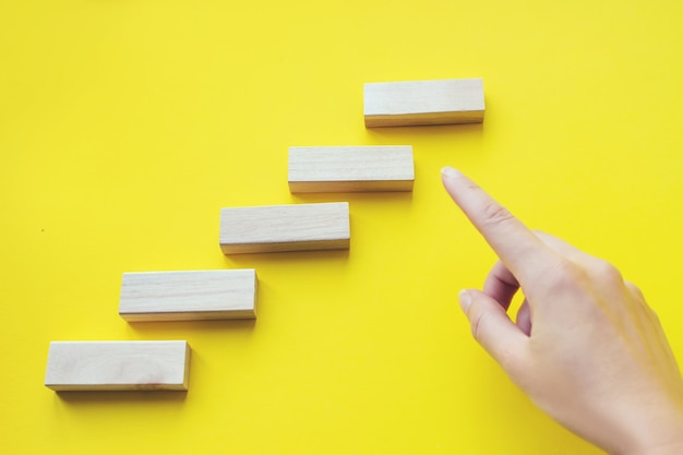Close up hand shows on wood block stacking as step stair. business concept growth success process