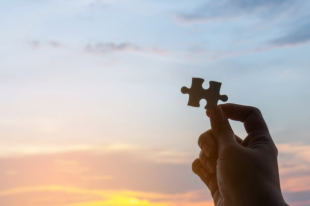 Close up hand of silhouette jigsaw puzzle last piece on hand , sky and sunset nature background - business solutions concept