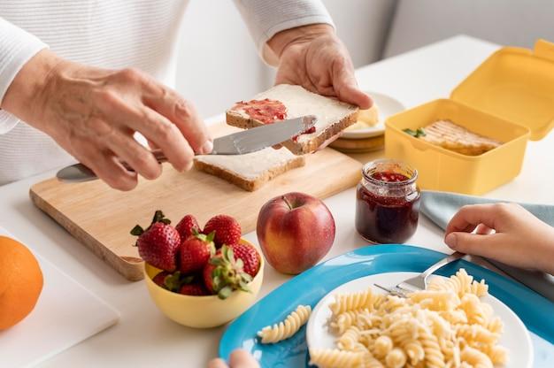 Chiuda sulla marmellata di diffusione della mano sul pane
