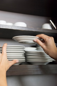 Close-up of hand stacking white saucer in the shelf