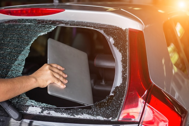 Close up hand stealing laptop from back side of car which rear glass broken