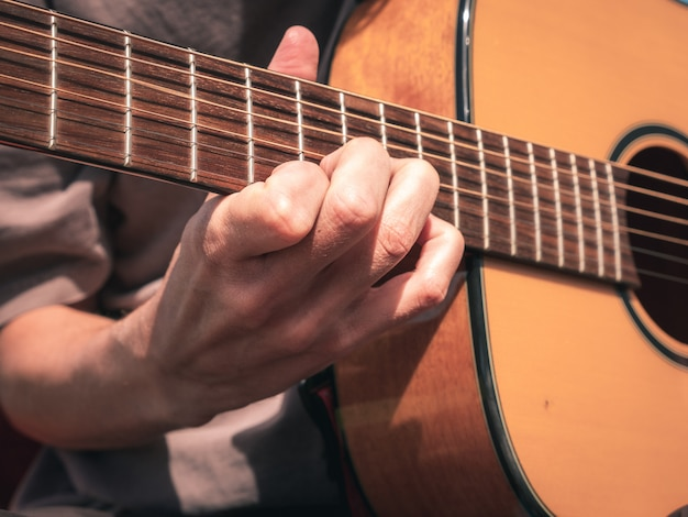 Close up hand on the strings of a lefty guitar