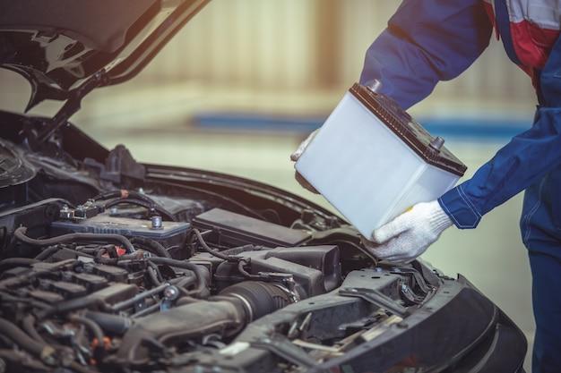 Крупным планом ручной техник или автомеханик меняет автомобильный аккумулятор в автосервисе.