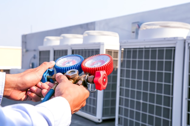 Close up hand of technician using manifold gauge to filling air conditioners.
