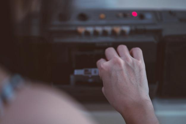 Закройте вверх руку, чтобы выбрать кассетный магнитофон. винтажный стиль