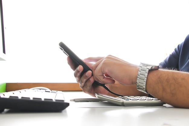Pcのぼやけたキーボードとワーキングオフィスのコンセプトでハンドタッチスマートフォンを閉じます。仕事とビジネスコンセプト。サラリーマン。