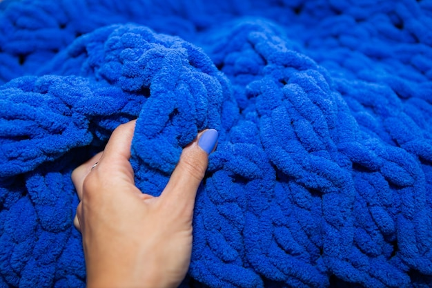 クローズアップ、手は美しい青い豪華なウールの毛布、暖かさと居心地のよさのコンセプト、碑文の場所に触れます。