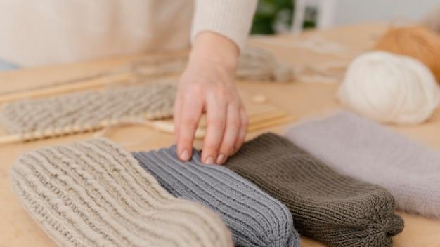 Cappelli lavorati a maglia toccanti della mano del primo piano