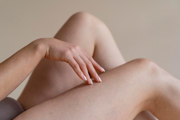 Close up hand touching leg