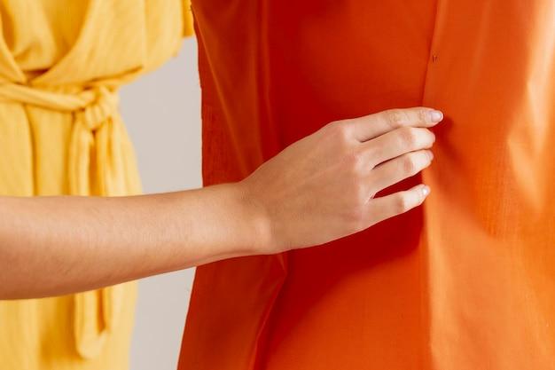 Close-up mano toccando un capo di abbigliamento