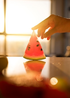 Close-up of hand touching the slice of watermelon on desk against sunlight