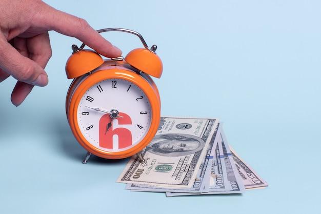 Крупным планом рука выключает будильник, банкноты на синем фоне
