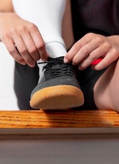 Крупным планом рука завязывает шнурки