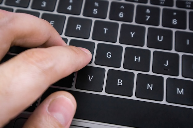 Close up of hand type on laptop keyboard