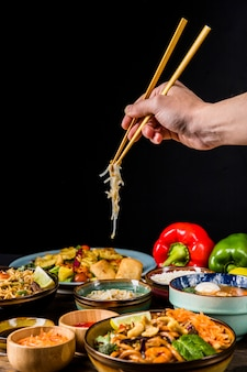 Close-up of hand using chopsticks to pick beans sprout against black background