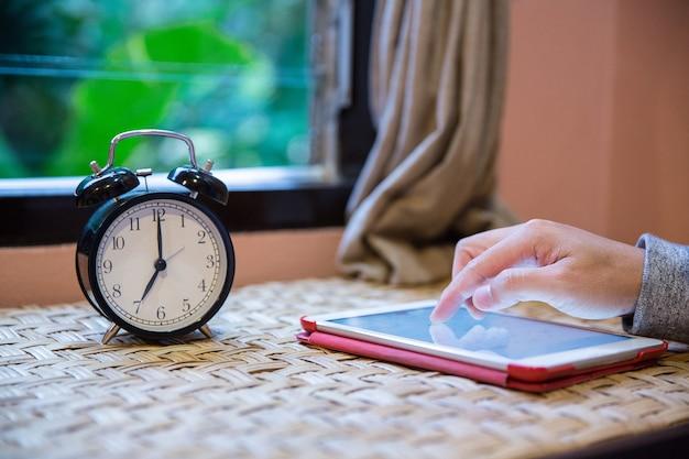 コンピュータのタブレットを使用して手を閉じ、ウィンドウの横のテーブルに目覚まし時計