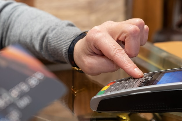 Close up of hand using credit card swiping machine to pay. hand with creditcard swipe through terminal for payment in cafeteria. man entering credit card code in swipe machine.