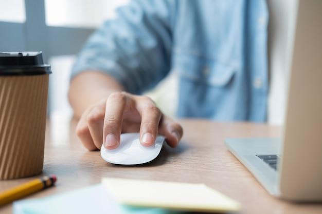 Закройте вверх по руке используя настольный компьютер компьютера мыши работая в офисе с концепцией технологии.